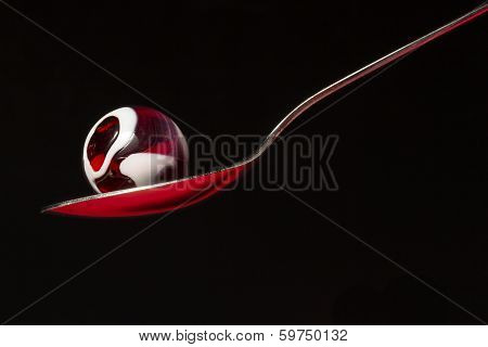 A red and white swirl marble on a spoon. poster