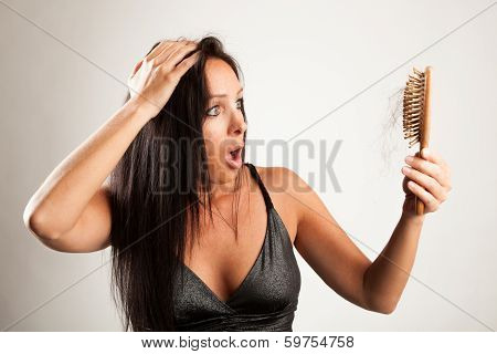 Beautiful woman is looking shocked to her hair bruch
