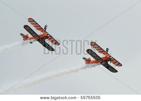 EASTBOURNE, ENGLAND - AUGUST 15, 2013: The Breitling wing walking display team perform at the Airbourne airshow. The team fly 1940s Boeing Stearman biplanes.
