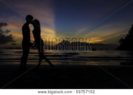 silhouettes of young loving couple kissing on tropical beach