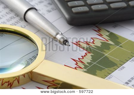 Pen, Magnifier And Calculator On Financial Statement