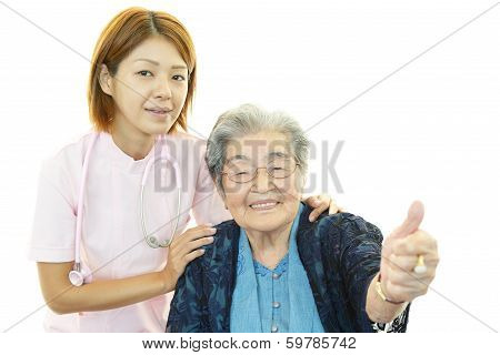 Smiling Asian nurse with old woman