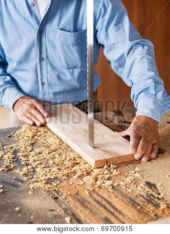 Midsection of senior carpenter cutting wood with bandsaw in workshop