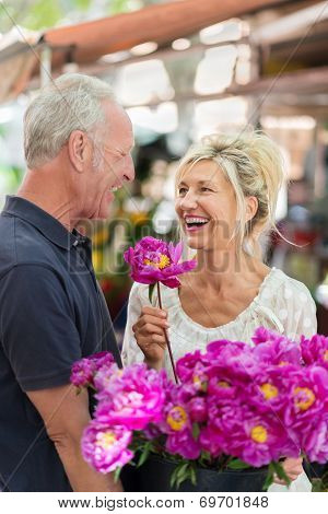 Laughing Vivacious Couple Celebrating With Flowers