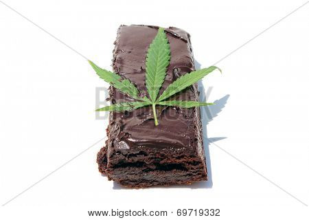 Genuine Medical Marijuana Chocolate Brownie, aka medical cannabis brownies, Pot Brownies or edibles. With a Genuine Marijuana Leaf in the frosting. Isolated on white with room for your text.