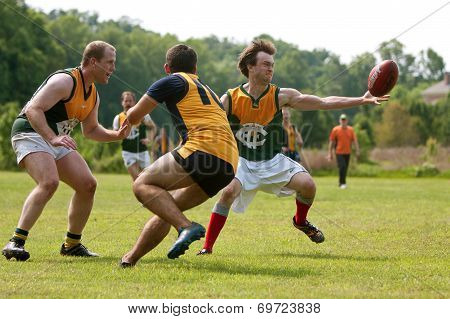 Player Reaches To Catch Ball In Australian Rules Football Game