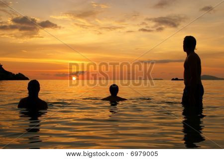 Three people waiting for the sunset