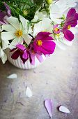 Vase with coreopsis flowers on the wooden table and good morning note poster