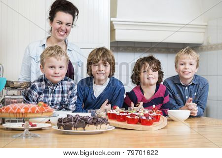 Portrait of happy group of kids, with desserts at kitchen counter
