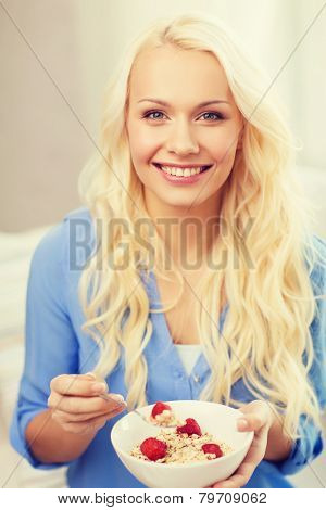 healthcare, food, home and happiness concept - smiling woman with bowl of muesli having breakfast at home poster