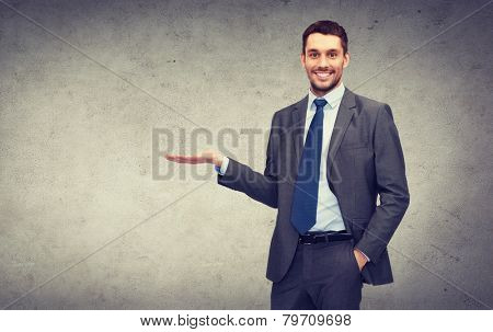 business, office, advertising and people concept - friendly young buisnessman showing something on the palm of his hand
