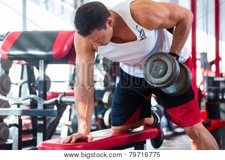 Bodybuilding man exercising lifting dumbbells in fitness club or gym
