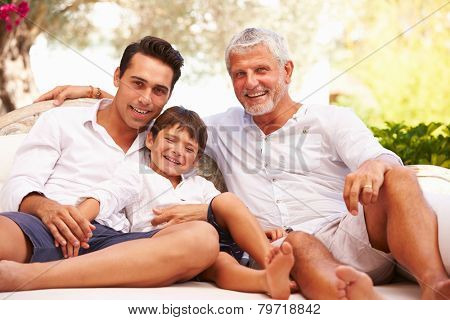 Grandfather,Father And Grandson Sitting Outdoors At Home
