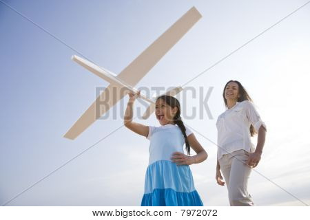 Mother And Daughter Having Fun With Toy Plane