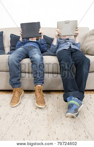 Two boys, slouching on a couch in a living room, each plaing games on a tablet computer.