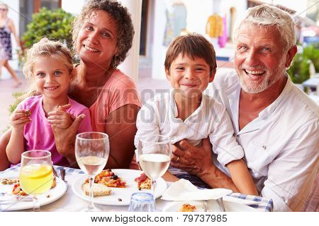 Grandparents With Grandchildren Eating Meal At Restaurant