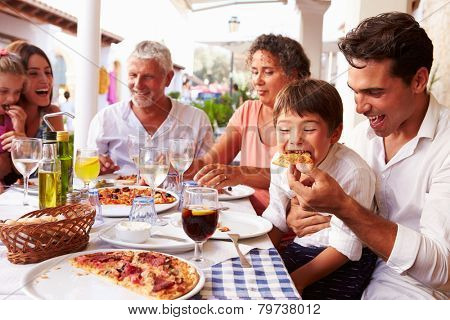 Multi Generation Family Eating Meal At Outdoor Restaurant