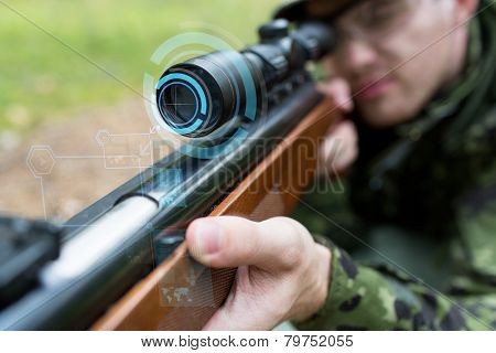 hunting, war, army, technology and people concept - close up of young soldier or sniper holding gun with virtual screen projection and aiming in forest poster