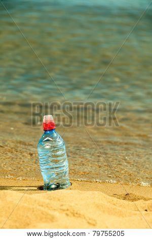 Bevarage. Bottle Of Water Drink On A Sandy Beach.