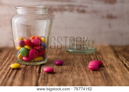 Color Chocolate Smarties In Glass Dose And Around On Wooden Board