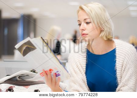 Woman reading a magazine while waiting.