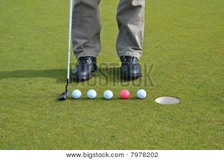 line of golf balls on a green