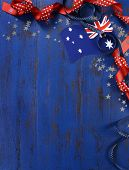 Happy Australia Day January 26 theme dark blue vintage distressed wood background with Australian flag and decorations with copy space for your text here vertical. poster