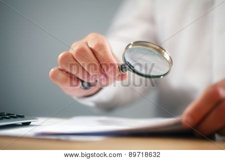 Businessman reading documents with magnifying glass concept for analyzing a finance agreement or legal contract