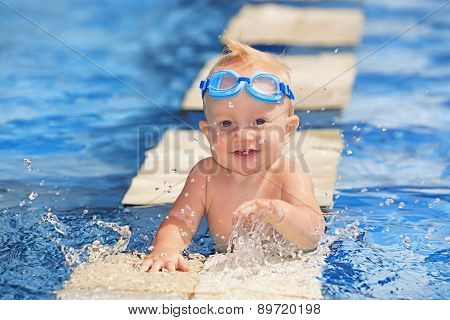 Happy Child Playing With Water Splashes In Pool
