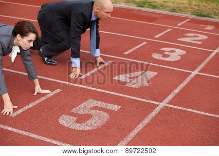 Businessman and woman on start line of running track