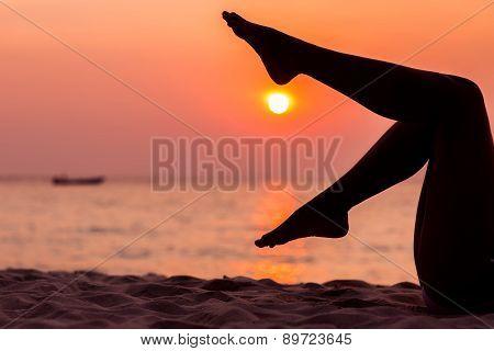 Female legs silhouette on sea background back lit