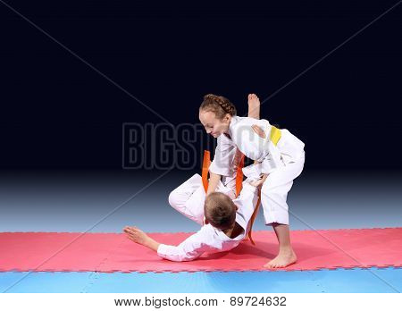 Girl and boy are trained judo throw on the mat poster