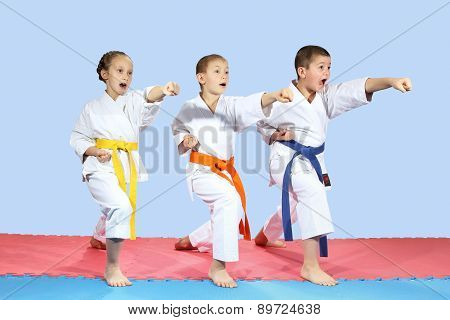 In karategi three athletes are hitting karate kick arm