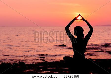 Woman silhouette sitting in lotus position on sea background back lit