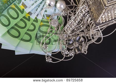 Silver jewelry and Euro on black
