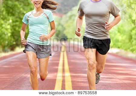 Health and fitness running. Runners on run training during fitness workout outside on road. People jogging together living healthy active lifestyle outside in summer. Midsection of woman and man.