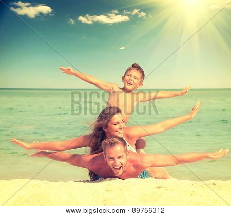 Happy Family Having Fun at the Beach. Joyful Family. Vacation and Travel concept. Summer Holidays. Parents with Son enjoying a holiday at the sea. Toned photo