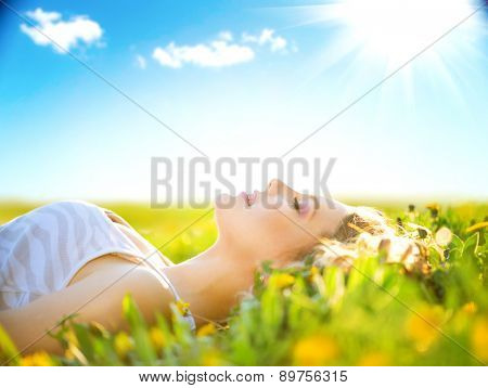 Beautiful Healthy Girl lying on summer field with flowers. Outdoors. Enjoy Nature. Healthy Smiling Girl on spring lawn. Allergy free concept. Freedom. Happy person outdoor poster
