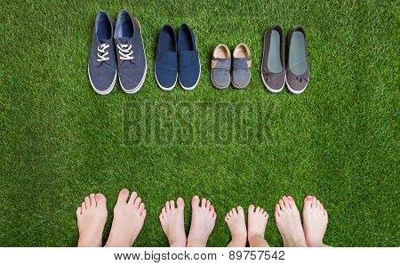 Family legs and shoes standing  on green grass
