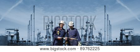 oil and gas engineers with large refinery in background, panoramic view