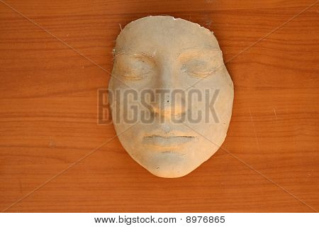 Theater mask made out of gips on wood poster