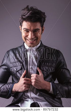 Haapy young fashion man smling to the camera while pulling his jacket.