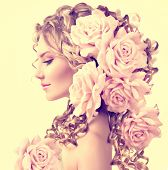Beauty girl with rose flowers hairstyle isolated on white background. Fashion model  woman portrait with pink flowers. Summer fairy portrait. Long permed curly hair. Perfect make up poster