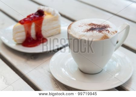 Cup of coffee with crepe cake on table