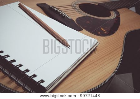 Pencil and paper on guitar in vintage style