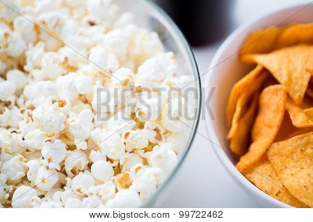 fast food, junk-food and unhealthy eating concept - close up of popcorn and corn crisps or nachos in bowls poster