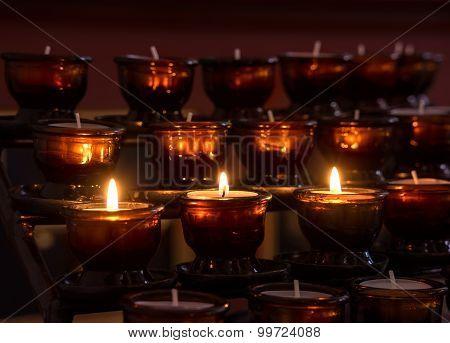 Three lit votive candles