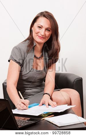 Smiling woman sitting with some documents