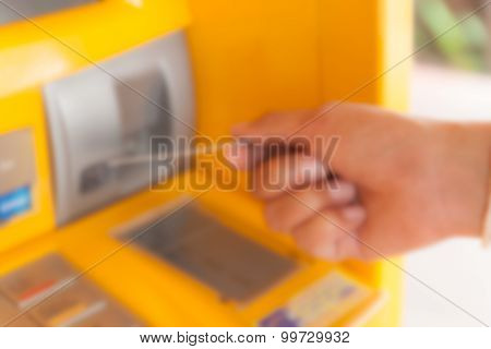 out of focus hand inserting ATM credit card into bank machine to withdraw money