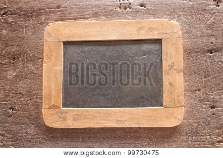Vintage style wood framed chalkboard over old wood background.